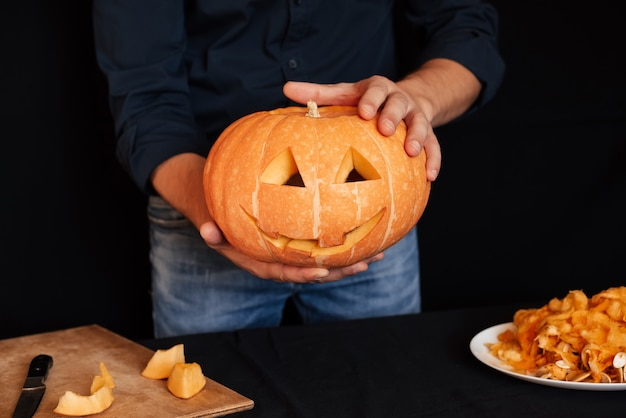 Pumpkin for halloween in the hands of men