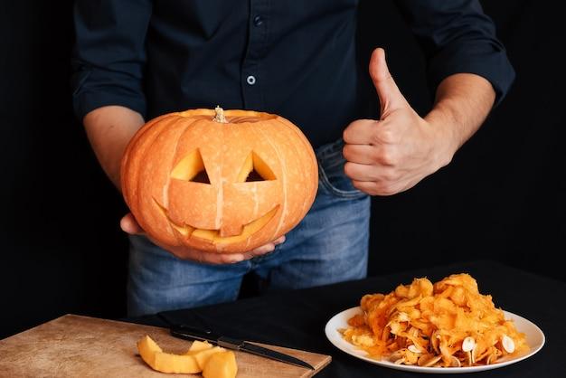 Pumpkin for halloween in the hands of men