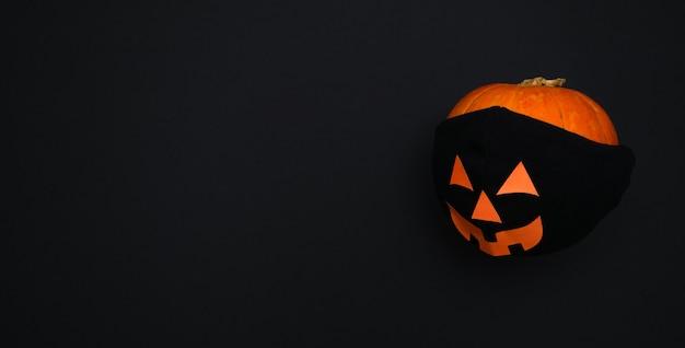 Тыква в черной защитной маске. хэллоуин и концепция covid-19.