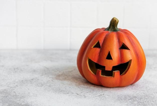 Pumpkin jackolantern with happy face funny smiling halloween pumpkin on concrete background