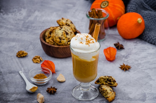 Pumpkin latte in a glass with spicy cream and a cinnamon stick on a gray stone surface with cookies with chocolate chips