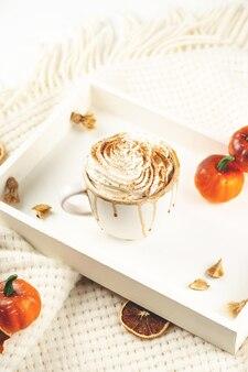 Тыквенный латте со взбитыми сливками и сиропом на белом подносе с пледом и маленьким осенним хэллоуинским п ...