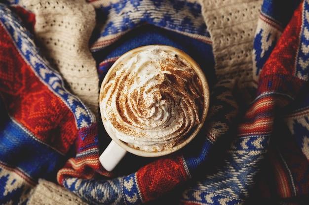 Тыквенный латте со взбитыми сливками и сиропом на народном вязаном свитере вид сверху плоской планировки