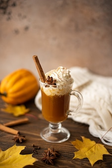 Pumpkin latte with whipped cream and cinnamon on a wooden table