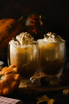 Тыквенный латте со взбитыми сливками в стаканах в стиле dark food. осень горячий пряный напиток на хэллоуин или день благодарения. выборочный фокус