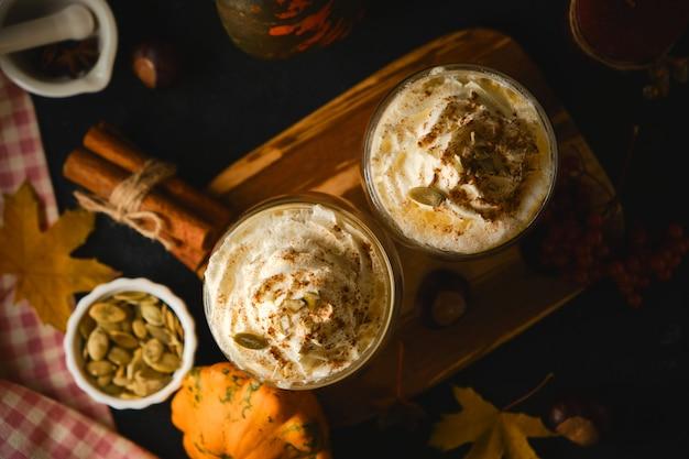 Тыквенный латте со взбитыми сливками в стаканах в стиле dark food. осень горячий пряный напиток на хэллоуин или день благодарения. вид сверху, выборочный фокус