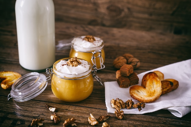 Тыквенный молочный коктейль в стеклянной банке со взбитыми сливками, ириской, ореховым и медовым печеньем