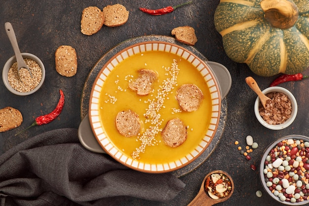 Pumpkin and mixed beans  creme soup in ceramic bowl, top view with ingredients