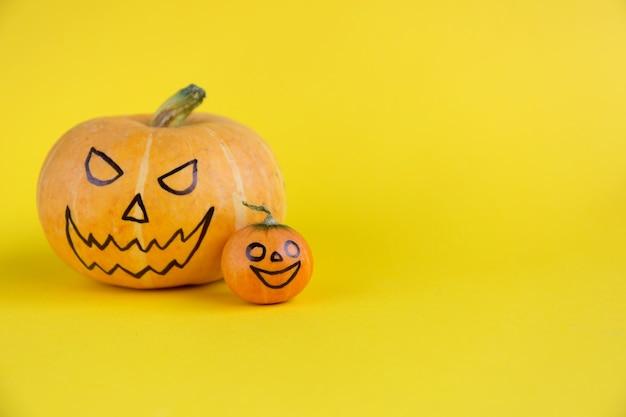 Тыква мать и ребенок со страшной улыбкой злые лица на желтом фоне концепции хэллоуин шаблон