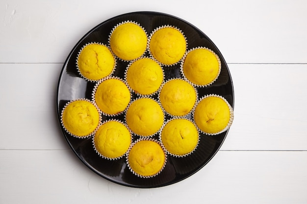 Pumpkin muffins on black plate on wooden table, flat lay. vegetable cupcakes on white background. top view. homemade bakery. plant-based food