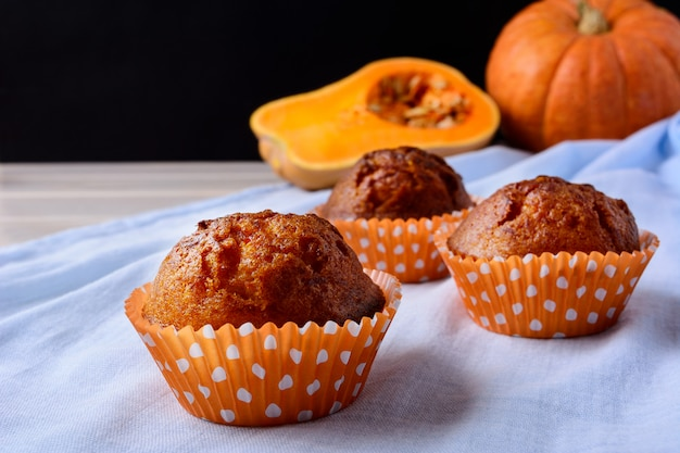 Pumpkin muffins in the orange wrappers on the blue napkin