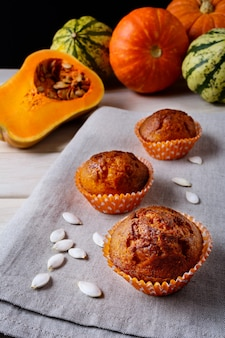 Pumpkin muffins in the orange wrappers with squash seeds