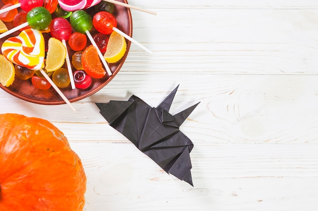 Pumpkin near bat origami and plate with bonbons
