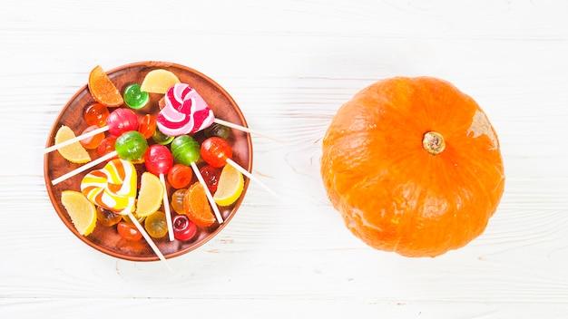 Pumpkin near plate with bonbons