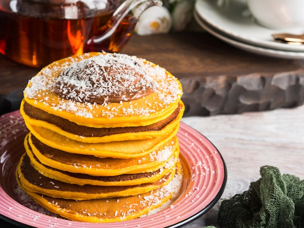 Pumpkin pancakes stack served with chocolate