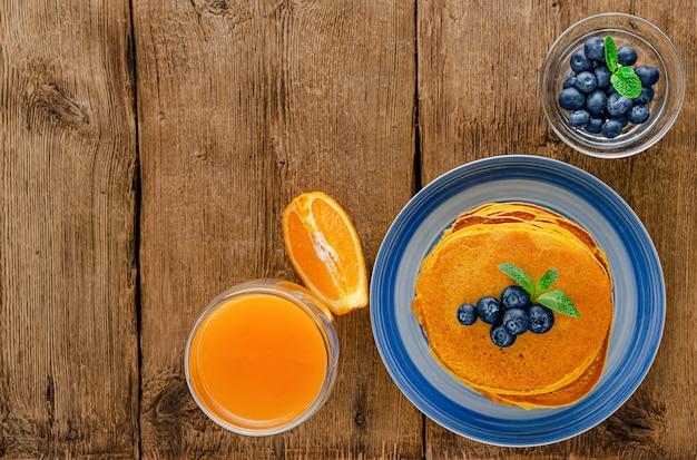素朴な木製のテーブルにブルーベリーとオレンジジュースとカボチャのパンケーキ。コピースペース。オーバーヘッド