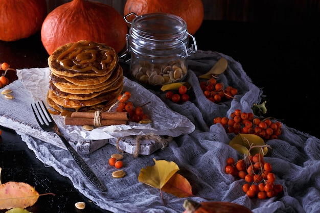 Pumpkin pancakes with caramel topping, with pumpkins, leaves  .