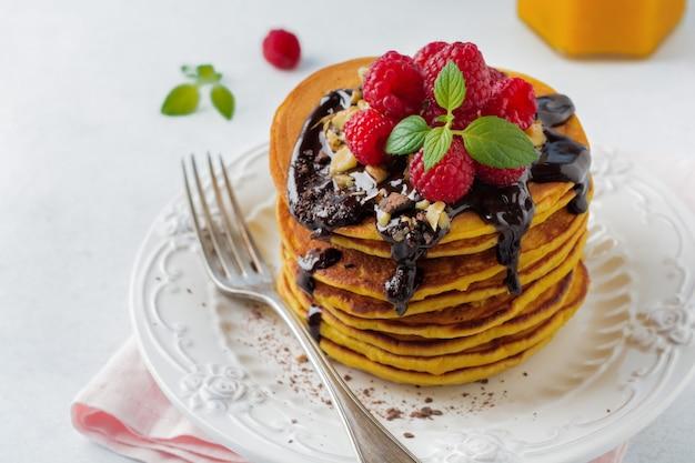 軽い石またはコンクリートの上に新鮮なラズベリー、チョコレート、クルミを添えたカボチャのパンケーキ。