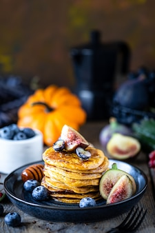 Pumpkin pancakes with syrup or honey, flax seeds, figs, blueberries in a dark plate on the table