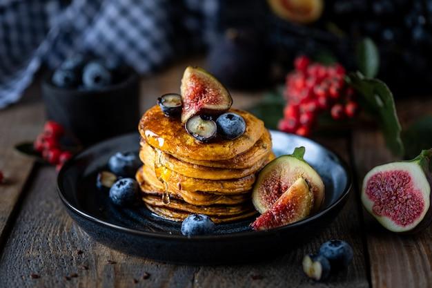 カボチャのパンケーキ、シロップまたは蜂蜜、亜麻の種子、イチジク、テーブルの上の暗いプレートのブルーベリー
