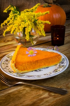 Pumpkin pie slice on the rustic wooden table
