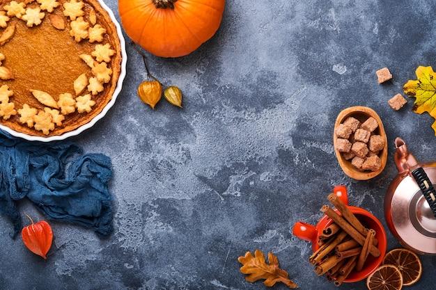 パンプキンパイ。素朴な背景にホイップクリームとシナモンのタルト。感謝祭やハロウィーンのための伝統的なアメリカの自家製カボチャケーキを食べる準備ができています。モックアップ。