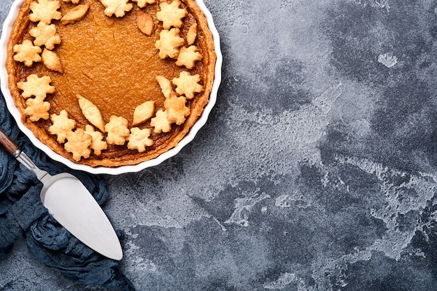 호박 파이. 소박한 배경에 휘핑크림과 계피를 넣은 타르트. 추수감사절이나 할로윈을 위한 전통적인 미국 수제 호박 케이크 먹을 준비가 되었습니다. 조롱.