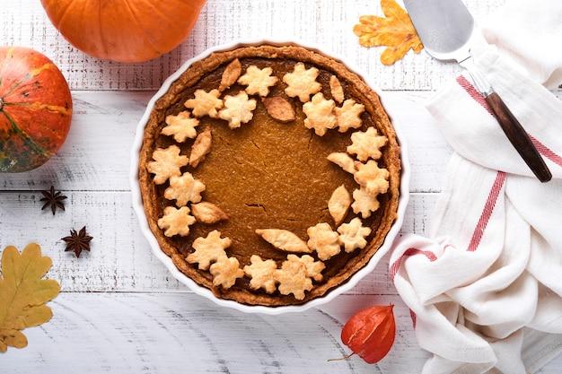 호박 파이. 흰색 소박한 배경에 휘핑크림과 계피를 넣은 타르트. 추수감사절이나 할로윈을 위한 전통적인 미국 수제 호박 케이크 먹을 준비가 되었습니다. 조롱.