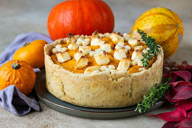 Pumpkin pie for thanksgiving day. savory pie with pumpkin and feta cheese decorated with thyme.