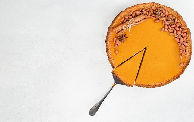 밝은 콘크리트 배경에 한 조각이 있는 호박 파이