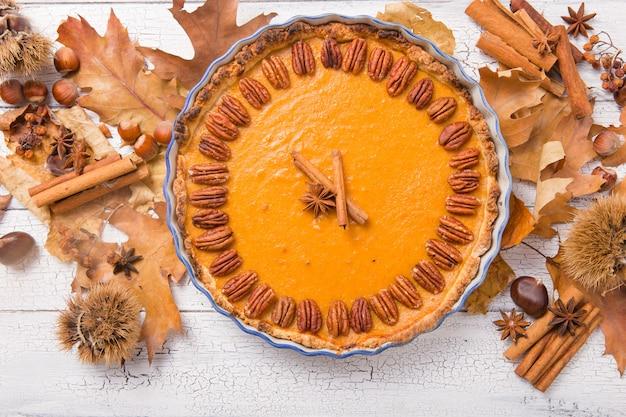Тыквенный пирог с орехом пекан и корицей на деревенском фоне. домашняя осенняя выпечка на день благодарения