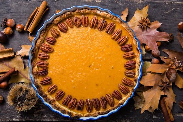 Пирог тыквы с гайкой пекана и циннамоном на деревенской предпосылке, взгляд сверху, космосе экземпляра. домашняя осенняя выпечка на день благодарения