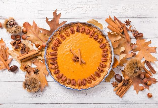 Пирог тыквы с орехом пекана и циннамоном на деревенской таблице, взгляд сверху, космосе экземпляра. домашняя осенняя выпечка на день благодарения