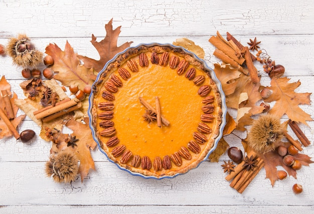 Pumpkin pie with pecan nut and cinnamon on rustic table, top view, copy space. homemade autumn pastry for thanksgiving