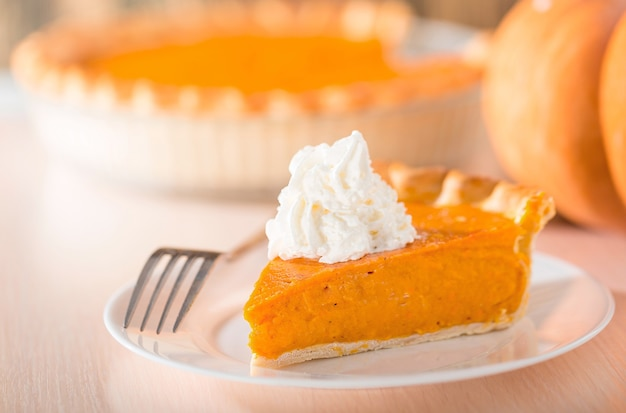 Pumpkin pie with swirls of whipped cream on decorative plate.