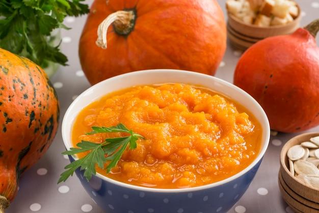 Pumpkin porridge in a bowl among orange pumpkins and seeds