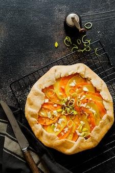 회색 콘크리트 테이블 표면에 호박, 감자, 죽은 태아의 치즈와 부추 galette 파이 접시. 평면도.