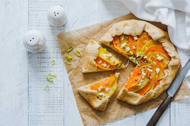 흰색 나무 테이블 표면에 호박, 감자, 죽은 태아의 치즈와 부추 galette 파이 접시. 평면도.