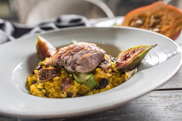 カボチャのリゾット焼き鴨胸肉のイチジクズッキーニとミンの葉イタリア料理または地中海料理