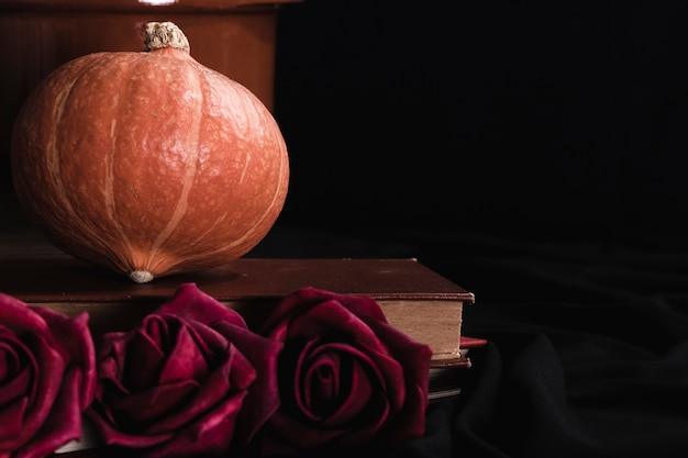 Pumpkin and roses on black background