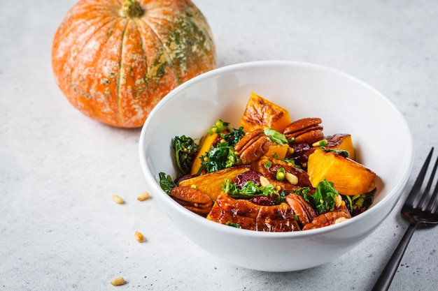 Pumpkin salad with nuts, cranberries and kale in a white bowl.