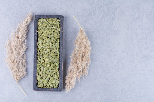 Pumpkin seed in a wooden plate next to pampas grass on marble.