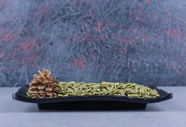 Тыквенные семечки и сосновая шишка на блюде на мраморной поверхности