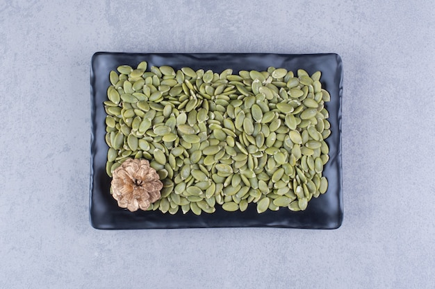 Тыквенные семечки и шишка на блюде на мраморе.