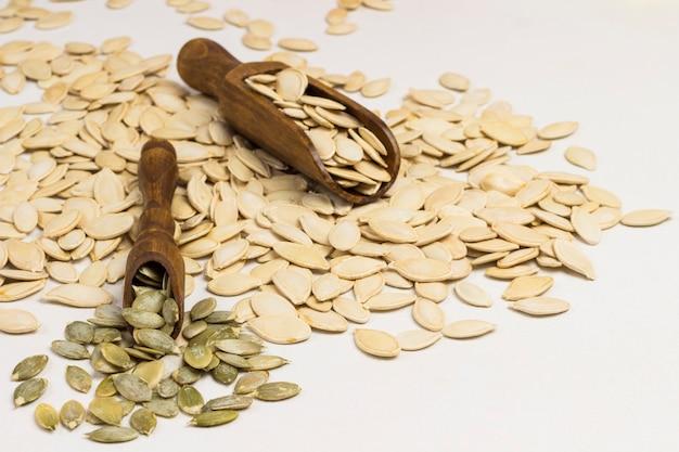 Семена тыквы и две деревянные ложки на белом фоне. источник кальция омега-3. концепция диетического питания.