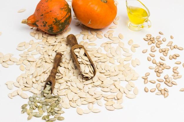 Тыквенные семечки и две деревянные ложки. оранжевые тыквы и масло. натуральный источник кальция, омега-3 и калия. концепция здорового питания.