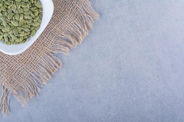 Semi di zucca in una ciotola su un tovagliolo di tela da imballaggio sulla superficie di marmo