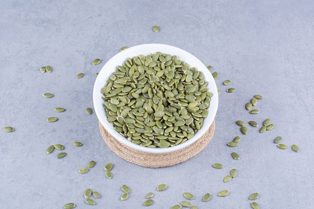 Pumpkin seeds in a bowl on a trivet on the marble surface
