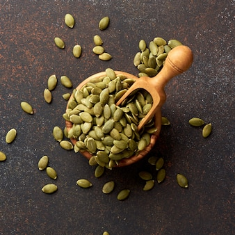 Pumpkin seeds on brown background.
