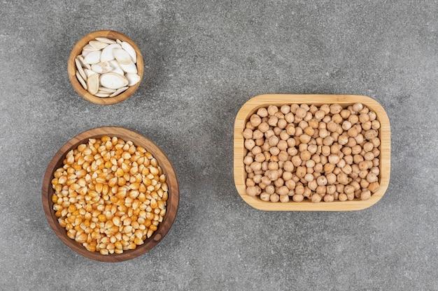 Ciotole di legno di semi di zucca, chicchi di mais e piselli.
